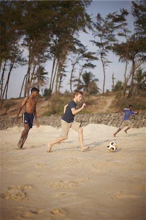Boys playing soccer on sandy beach Stock Photo - Premium Royalty-Free, Code: 6122-07705972