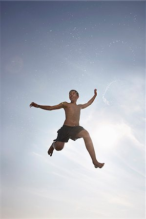 shirtless teen boy - Boy posing in mid-air Stock Photo - Premium Royalty-Free, Code: 6122-07705999