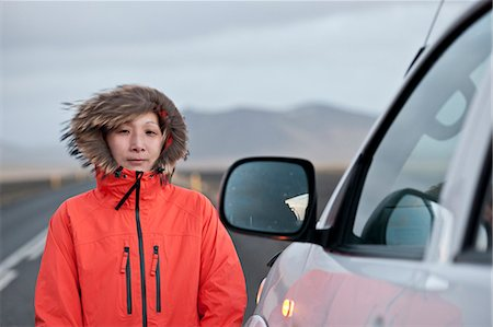 Woman standing outside car on rural road Stock Photo - Premium Royalty-Free, Code: 6122-07706059