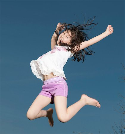 Smiling girl jumping for joy outdoors Stock Photo - Premium Royalty-Free, Code: 6122-07706064
