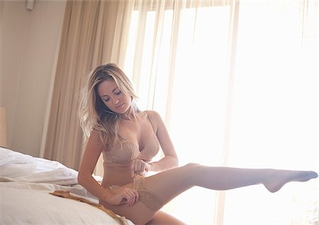 Woman pulling on pantyhose on bed Stock Photo - Premium Royalty-Free, Code: 6122-07706096
