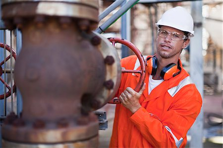 pipe (industry) - Worker adjusting gauge at oil refinery Stock Photo - Premium Royalty-Free, Code: 6122-07706253