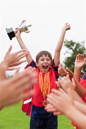 Children cheering teammate with trophy Stock Photo - Premium Royalty-Free, Code: 6122-07706215