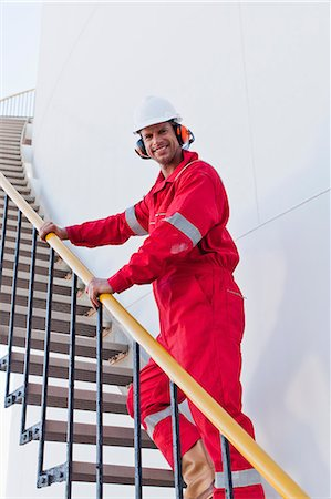 Worker climbing steps at chemical plant Stock Photo - Premium Royalty-Free, Code: 6122-07706304
