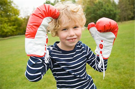 Boy playing with boxing gloves outdoors Stock Photo - Premium Royalty-Free, Code: 6122-07706548