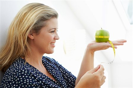 Smiling woman measuring apple Stock Photo - Premium Royalty-Free, Code: 6122-07706574