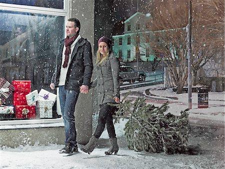 snow christmas tree white - Couple carrying Christmas tree in snow Stock Photo - Premium Royalty-Free, Code: 6122-07706505