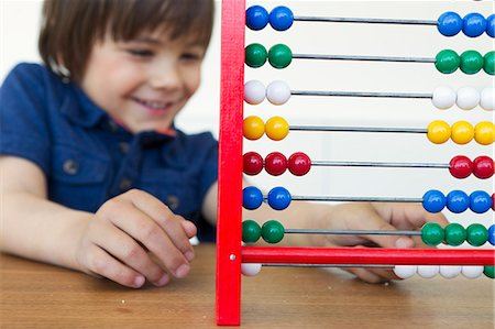 Smiling boy playing with abacus Stock Photo - Premium Royalty-Free, Code: 6122-07706675