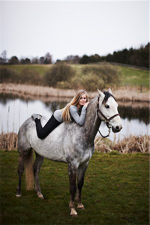 Girl laying on horse in field Stock Photo - Premium Royalty-Free, Code: 6122-07706958