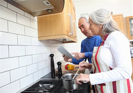 Older couple cooking together in kitchen Stock Photo - Premium Royalty-Free, Code: 6122-07707305