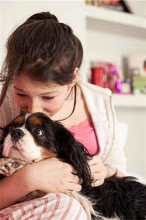 preteen kissing - teenage girls playing with dog at home Stock Photo - Premium Royalty-Free, Code: 6122-08211939
