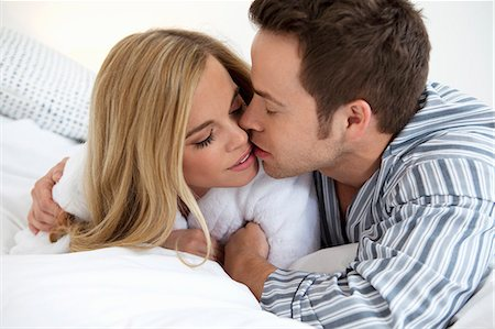 Couple in bathrobes kissing on bed Stock Photo - Premium Royalty-Free, Code: 6122-08212197