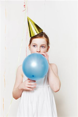 Girl in party hat, blowing up balloon Stock Photo - Premium Royalty-Free, Code: 6122-08212873