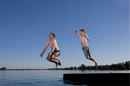 Father and son jumping into lake Stock Photo - Premium Royalty-Free, Code: 6122-08229045