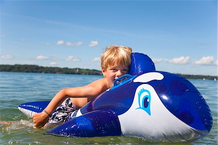 Boy floating in lake with toy whale Stock Photo - Premium Royalty-Free, Code: 6122-08229341