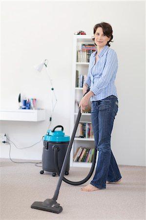 Smiling woman vacuuming living room Stock Photo - Premium Royalty-Free, Code: 6122-08229478