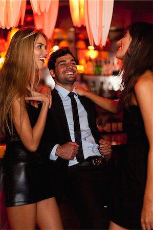 Women talking with man in bar Stock Photo - Premium Royalty-Free, Code: 6122-08229504