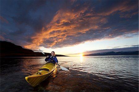 Woman kayaking in still lake Stock Photo - Premium Royalty-Free, Code: 6122-08229532