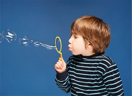 Close up of boy blowing bubbles Stock Photo - Premium Royalty-Free, Code: 6122-08229768