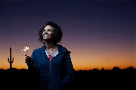 Woman playing with sparkler in desert Stock Photo - Premium Royalty-Free, Code: 6122-08229712