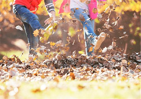 pile leaves playing - Boy and girl kicking in autumn leaves Stock Photo - Premium Royalty-Free, Code: 6124-08170347