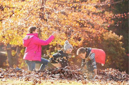 pile leaves playing - Boys and girl playing in autumn leaves Stock Photo - Premium Royalty-Free, Code: 6124-08170349
