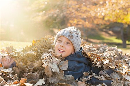 pile leaves playing - Portrait smiling boys covered in autumn leaves Stock Photo - Premium Royalty-Free, Code: 6124-08170364