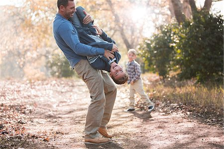 Playful father lifting son upside-down on path in woods Stock Photo - Premium Royalty-Free, Code: 6124-08170371