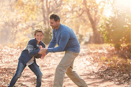 Playful father and son on path in woods Stock Photo - Premium Royalty-Free, Code: 6124-08170372