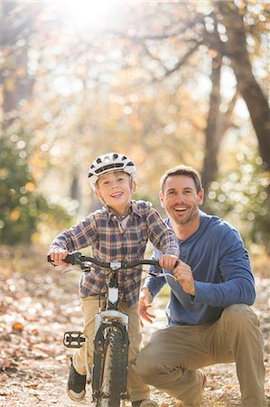 father with two sons not girls - Portrait smiling father teaching son to ride a bike in woods Stock Photo - Premium Royalty-Free, Code: 6124-08170443