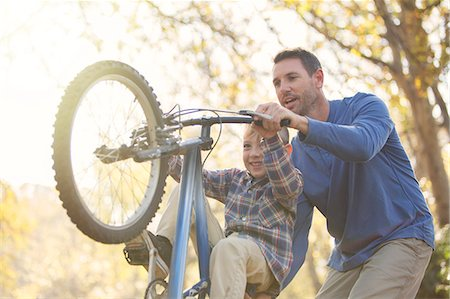 Father teaching son wheelie on bicycle Stock Photo - Premium Royalty-Free, Code: 6124-08170441