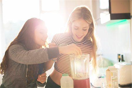 Teenage girls making smoothie in sunny kitchen Stock Photo - Premium Royalty-Free, Code: 6124-08170491