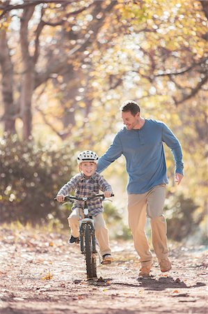 Father teaching son to ride a bicycle on path in woods Stock Photo - Premium Royalty-Free, Code: 6124-08170400