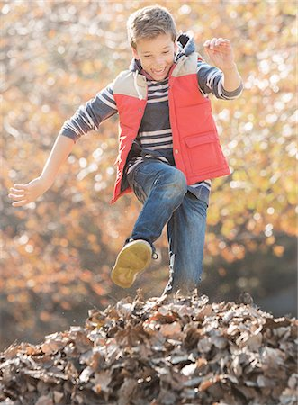 pile leaves playing - Enthusiastic boy jumping over pile of autumn leaves Stock Photo - Premium Royalty-Free, Code: 6124-08170409