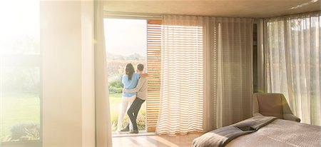 rich lifestyle - Couple hugging at patio doorway in bedroom Stock Photo - Premium Royalty-Free, Code: 6124-08170660