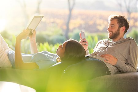 Couple laying and using digital tablet and cell phone on sunny patio Stock Photo - Premium Royalty-Free, Code: 6124-08170664