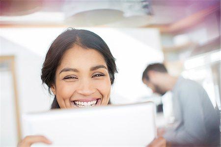 Close up portrait smiling woman using digital tablet Stock Photo - Premium Royalty-Free, Code: 6124-08170688