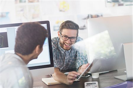Creative designers talking between computers in office Stock Photo - Premium Royalty-Free, Code: 6124-08170796