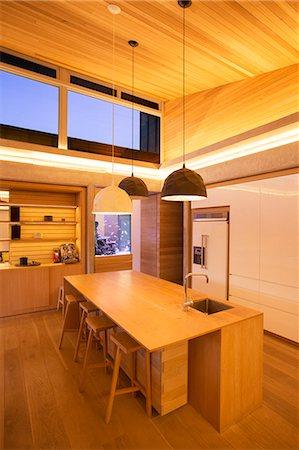 photography - Illuminated slanted wood ceiling and pendant lights over kitchen island Stock Photo - Premium Royalty-Free, Code: 6124-08170708