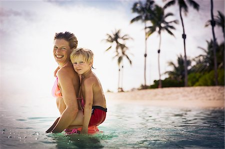 Portrait smiling mother piggybacking son in tropical ocean Stock Photo - Premium Royalty-Free, Code: 6124-08658148