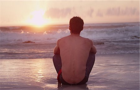 Pensive young man on beach watching sunset over ocean Stock Photo - Premium Royalty-Free, Code: 6124-08658135
