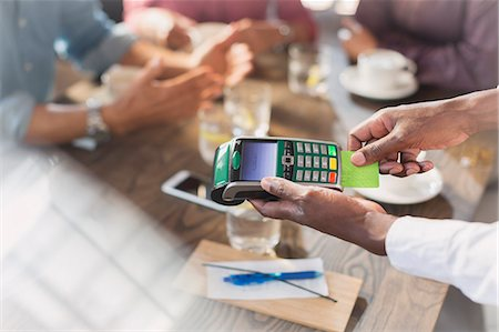 Waiter using credit card reader at restaurant table Stock Photo - Premium Royalty-Free, Code: 6124-08743179