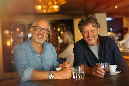 Portrait smiling men drinking coffee and water at restaurant table Stock Photo - Premium Royalty-Free, Code: 6124-08743198