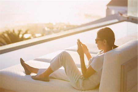 Woman using cell phone on chaise lounge at poolside on luxury patio Stock Photo - Premium Royalty-Free, Code: 6124-08743366