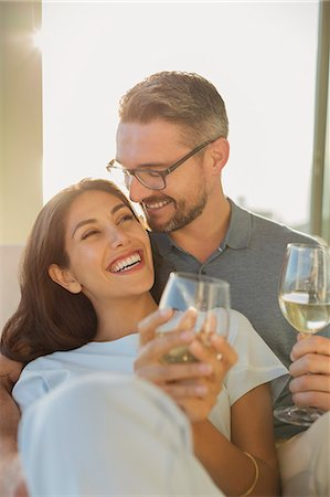 Affectionate couple smiling and drinking white wine Stock Photo - Premium Royalty-Free, Code: 6124-08743370