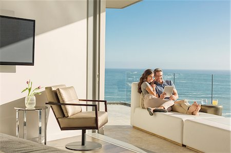 Couple using digital tablet on chaise lounge on sunny luxury balcony with ocean view Stock Photo - Premium Royalty-Free, Code: 6124-08743381