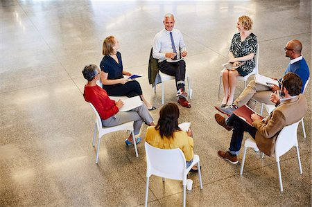 Business people talking in meeting circle Stock Photo - Premium Royalty-Free, Code: 6124-08768385