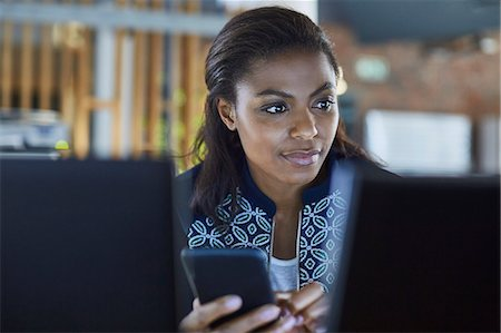 Businesswoman texting at computer in office Stock Photo - Premium Royalty-Free, Code: 6124-08768429