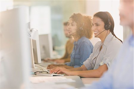 Smiling businesswoman with headset working at computer in office Stock Photo - Premium Royalty-Free, Code: 6124-08703921