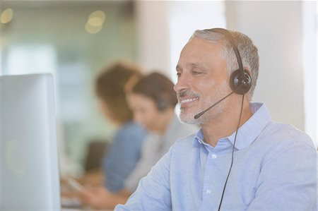 Businessman with headset working at computer in office Stock Photo - Premium Royalty-Free, Code: 6124-08703930